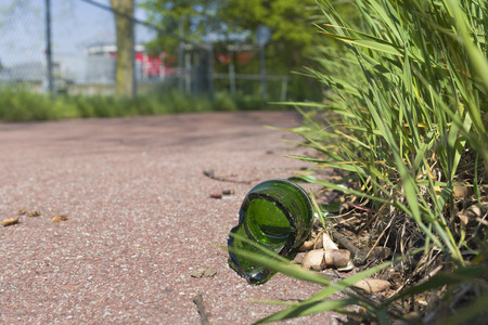 broken green bottle on a bicycle path