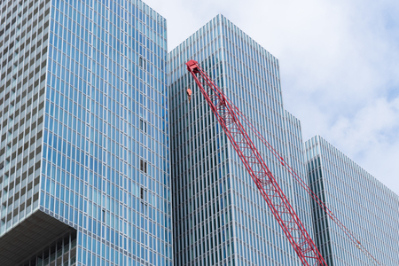 oma: ROTTERDAM, NETHERLANDS - MAY 14, 2016: Construction crane in front of the famous skyscraper the rotterdam. It is a multifunctional building on the Wilhelmina Pier designed by O.M.A., the office of architect Rem Koolhaas.