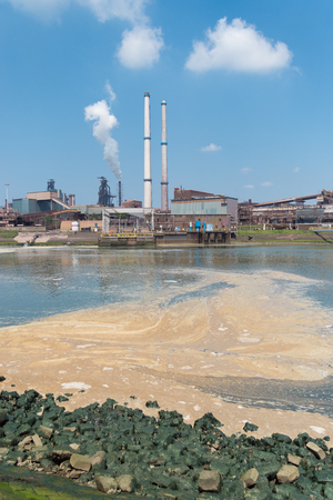 polluted water with a large steel plant in the background