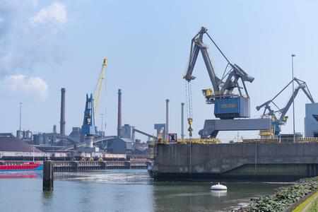 přístavní jeřáb vykládat loď před velkou ocelárnou