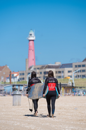 SCHEVENINGEN, NETHERLANDS - JULY 3, 2016: Two surf girls carrying their surfboards at the dutch north sea coast Editorial