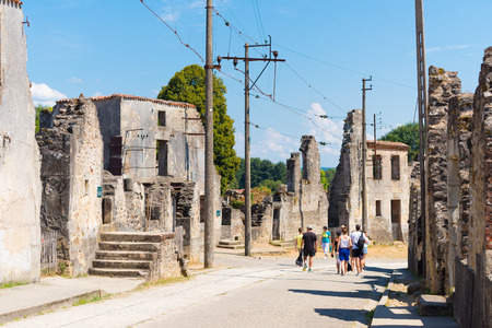 nazis: ORADOUR-SUR-GLANE, FRANCE - AUGUST 15, 2016: Tourists between the ruins of the by the nazis destroyed french village in WW2 Editorial