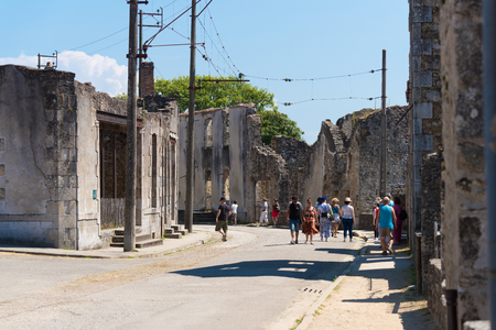 tribute: ORADOUR-SUR-GLANE, FRANCE - AUGUST 15, 2016: Tourists between the ruins of the by the nazis destroyed french village in WW2 Editorial