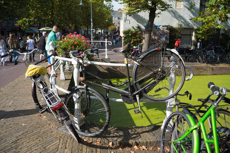 DELFT, NETHERLANDS - SEPTEMBER 18, 2016: Various bicycles parked on a small bridge in the center of Delft