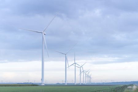 row of wind turbines in early morning in a flat dutch landscape Stock Photo