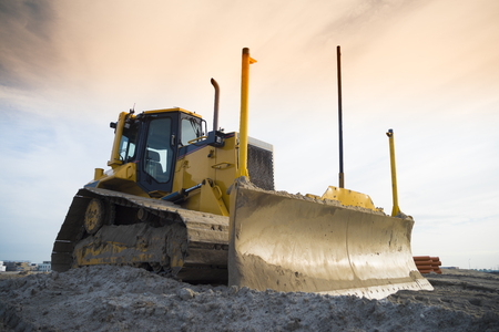 machinery: yellow excavator on a construction site in front of an orange sky