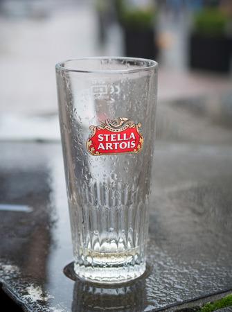 ANTWERP, BELGIUM - OCTOBER 2, 2016: Empty glass of Stella Artois beer on a rainy wet table. It is a pilsner brewed in Leuven Belgium since 1926 Editorial
