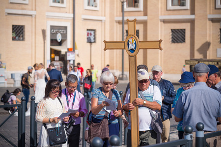 VATICAN CITY, VATICAN - OCTOBER 16, 2016: Group of unknown pilgrims carrying a cross in front of the saint peters basilica Editorial