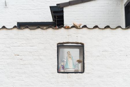 白いレンガの壁に聖母マリアと小さなボックス 写真素材