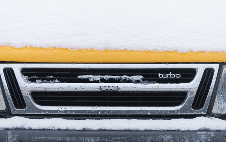 OLDENZAAL, NETHERLANDS - JANUARY 15, 2017: Detail of a yellow vintage Saab 900 turbo S convertible in snowy conditions. Sajtókép