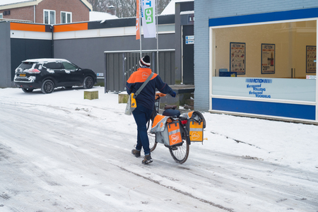 OLDENZAAL, NETHERLANDS - JANUARY 7, 2017: Unknown female mail deliverer walking next to her bike because of a snowy road. Editoriali