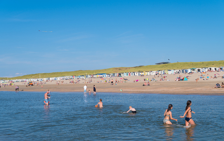 WIJK AAN ZEE, NETHERLANDS - AUGUST 27, 2017: Children having fun playing in sea during a warm summer day