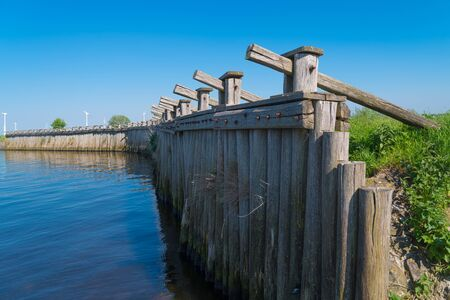 Since the first constructed dikes at the Zuiderzee did not offer sufficient protection against the water, the dikes were reinforced in several places with a pile construction from the 15th century. Long rows of posts of oak and / or coniferous wood were placed next to each other at the pile dike, which were mutually connected and anchored in the ground by means of cross beams. Stock Photo