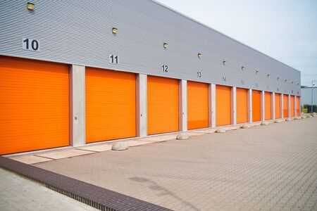 exterior of a commercial warehouse with orange roller doors