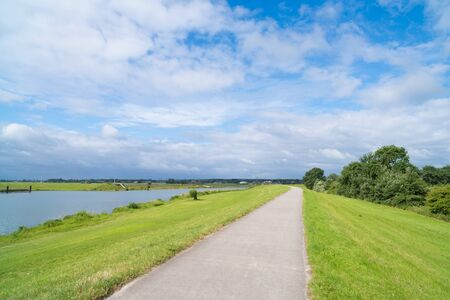 empty bicycle path over a dike along the Ijssel river in the Netherlands Stock Photo