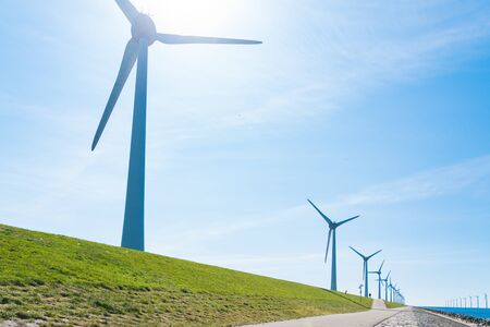 row of windmills on a dutch dike Stock Photo