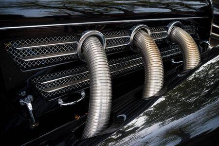 three chrome exhaust pipes on a black oldtimer car
