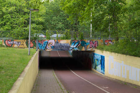 OLDENZAAL, NETHERLANDS - MAY 18, 2019: Bicycle and pedestrian tunnel cheered up with all kinds of graffiti Editorial