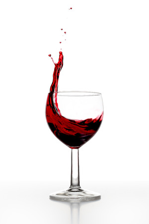 A glass with red wine, red wine splashes out of the glass Stock Photo