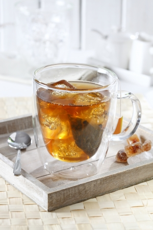 Glass of iced tea on tray with spoon and sugar and blurred background photo