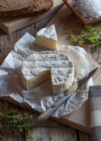 penicillium: A piece of camembert cheese on a cutting board with a knife and herbs.