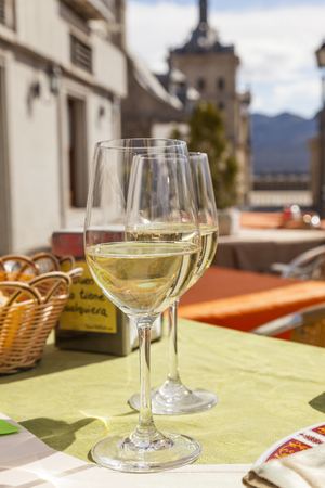spain: Enjoying a cool white wine at a cafe in Escorial, Spain Stock Photo