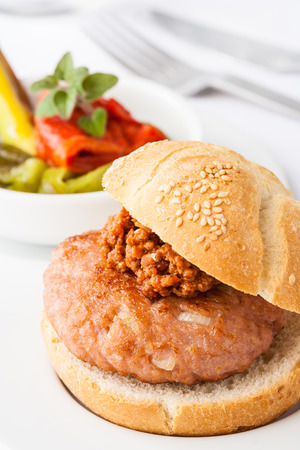 bolognese sauce: A small gourmet hamburger with side dish and Bolognese sauce Stock Photo
