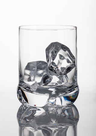 scotch whisky: An empty whisky glass with ice cubes