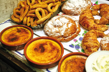 crema: Crema catalana, popular Catalan cold custard recipe with a crispy caramel coating. On the background churros and ensaimadas