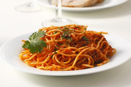 spaghetti bolognese: A dish of spaghetti bolognese served on a table