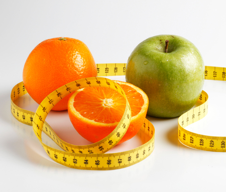 loose weight: Cut orange and green apple with yellow measure tape