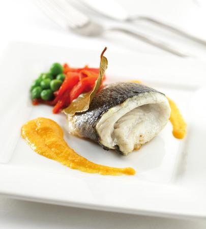 Zeebaarsfilet op een bord met saus, paprika en groene erwten.