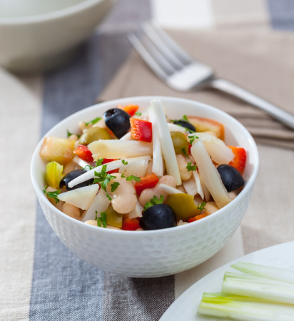 endive: A bowl of bean salad with endive, bell pepper, onion, olives and parsley Foto de archivo