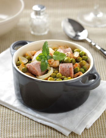 sausage pot: Green pea stwe in a small ceramic cooking pot with onions, carrot and sausage. Stock Photo