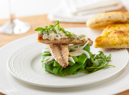 A delicious salad with green beans, rocket leaves, onion, mackerel and tartar sauce Stock Photo