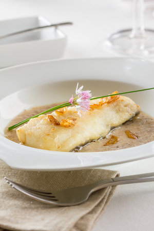 hake: A fried hake fillet served a garlic sauce and garnished with fried garlic slices.