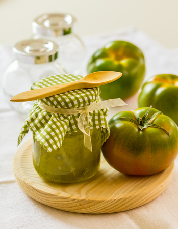 chutney: Green tomato chutney in a jar on a wooden surface Stock Photo