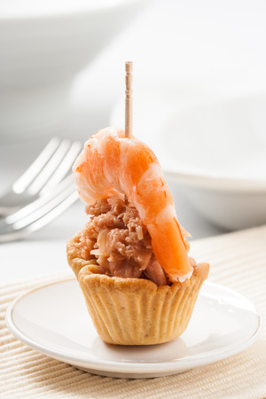 tunafish: A tartlet appetizer filled with tuna fish and garnished with a shrimp.