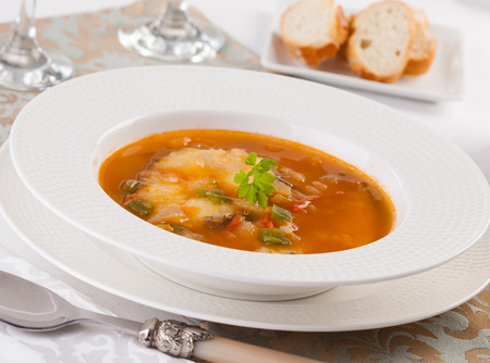 Hungarian fish soup on a plate with bread.
