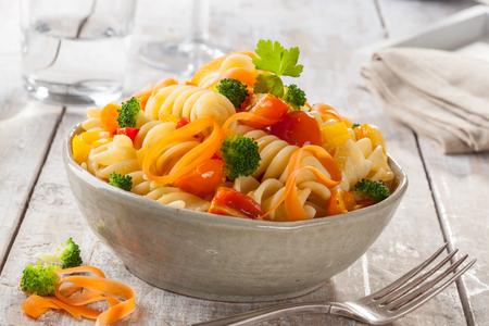 Fusilli-Teigwaren mit bunten Tomaten, Karotten und Brokkoli auf einer italienischen Küche des weißen Holztischs. Standard-Bild - 69132044
