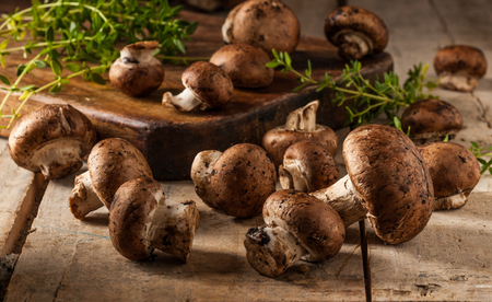 agaricus: Portobello mushrooms on a wooden table with a cutting board and herbs. Selective focus. Stock Photo