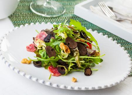 A delicious salad with arugola, black truffle, black olives, salami, walnuts