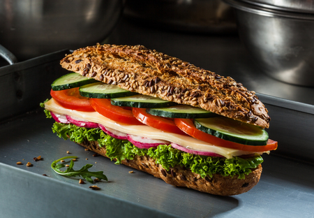 Sandwich with cheese, tomato, cucumber, radish and lettuce. Dark and moody.