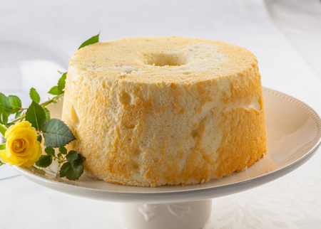 an icing: Angel food cake, or angel cake, is a type of sponge cake made with stiffly beaten egg whites with no addition of butter. Stock Photo
