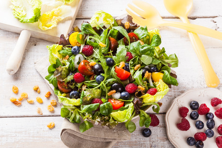 Fresh green salad with raspberries and blueberries on a white wooden table. Stock Photo