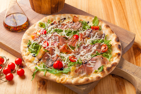 Pizza with dried ham, rocket leaves, tomato and Parmesan cheese on a cutting board.