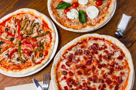 Several different pizzas on a wooden restaurant table. Banco de Imagens