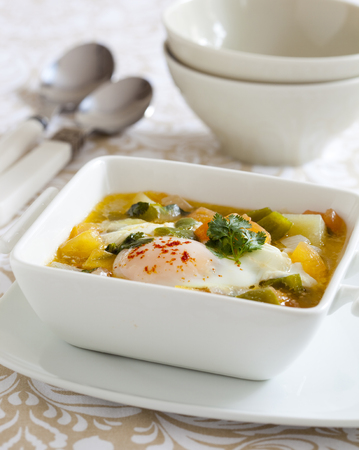 Fish stew with coriander leaves an a poached egg