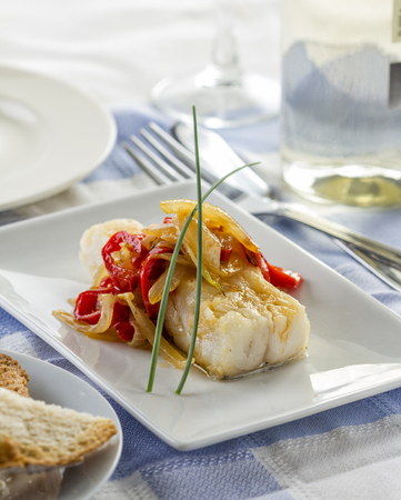 Delicious fried cod fillet with onions and bell pepper.