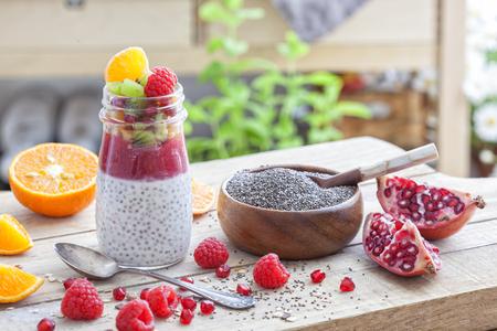 チア種子、マンゴー、穀物、ラズベリーとキウイと瓶の中の健康的なデザート。